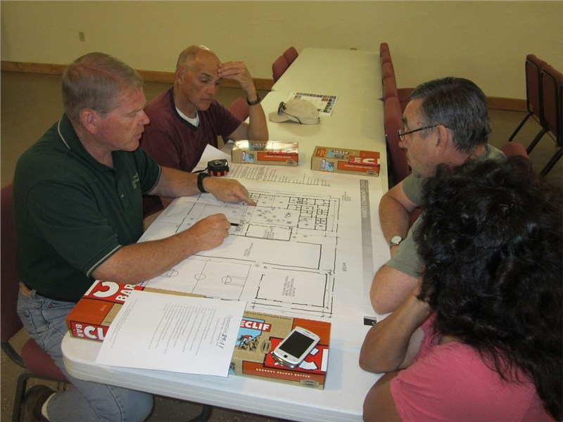 Randy, Bo, Pastor Stan Patterson and his wife Maxine discuss the latest drawings for the proposed women's shelter and site improvement plan for Pure Heart Bible Church in Kaibeto AZ.