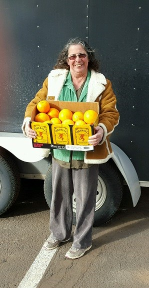 Marsha for the Forgotten People accepting the fresh oranges