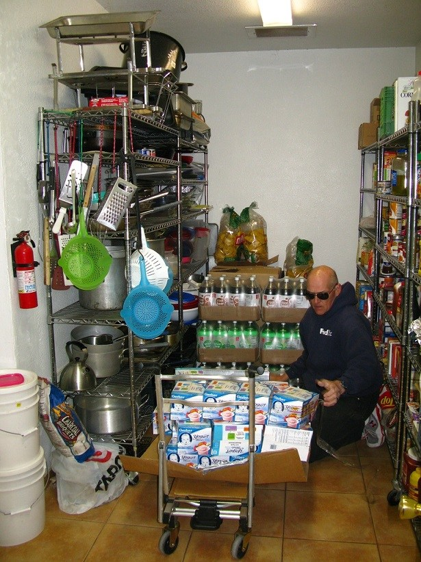 Bo unloading food in the NAOMI House pantry