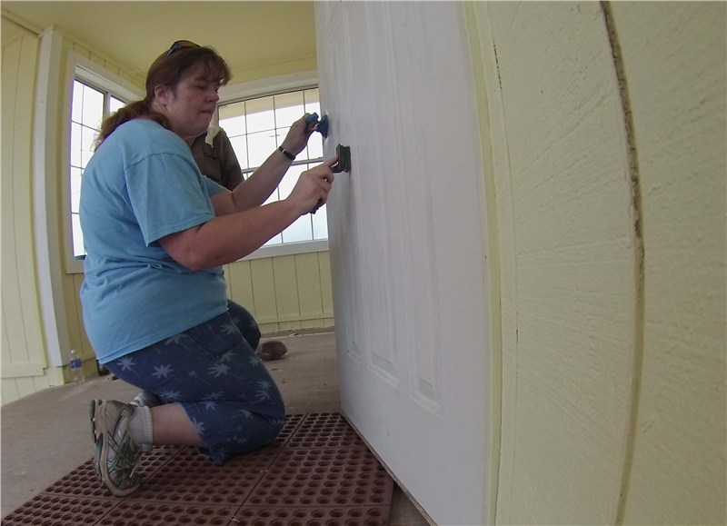 Pastor Kristi working on the churches entry doors